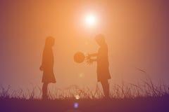 Silhouettez les enfants jouant le football sur le coucher du soleil de ciel Temps dessus Image stock
