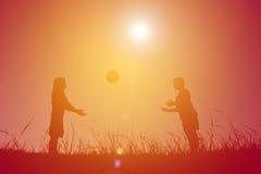 Silhouettez les enfants jouant le football sur le coucher du soleil de ciel Temps dessus Image libre de droits