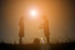Silhouettez les enfants jouant le football sur le coucher du soleil de ciel Temps dessus Photographie stock libre de droits