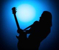 Silhouettez les guitaristes d'un groupe de rock avec la guitare sur le fond bleu Image stock