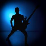 Silhouettez les guitaristes d'un groupe de rock avec la guitare sur le fond bleu Photographie stock