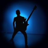 Silhouettez les guitaristes d'un groupe de rock avec la guitare sur le fond bleu Photo stock