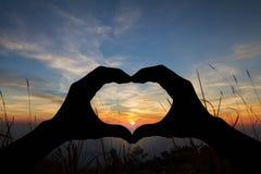 Silhouettez les mains en forme de coeur faisant des gestes sur le coucher du soleil brouillé au-dessus de la montagne Photo stock