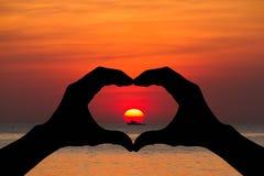 Silhouettez les mains en forme de coeur faisant des gestes sur le coucher du soleil brouillé au-dessus de la plage Photos libres de droits