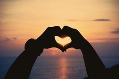 Silhouettez les mains humaines dans le symbole de coeur formé au coucher du soleil Images stock