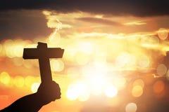 Silhouettez les mains humaines tenant un saint croisé et prié pour bénissez Photos stock