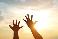 Silhouettez les mains mère et fils sur le fond de coucher du soleil Photos stock