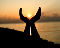 Silhouettez les mains vides ouvertes d'humain avec des paumes au-dessus du soleil Photo libre de droits