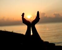 Silhouettez les mains vides ouvertes d'humain avec des paumes au-dessus du soleil Image stock
