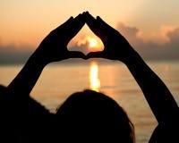 Silhouettez les mains vides ouvertes d'humain avec des paumes au-dessus du soleil Photo stock