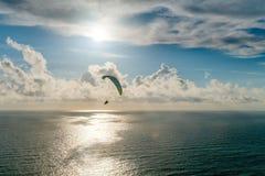 Silhouettez les parapentistes tandem volants au-dessus de la mer au coucher du soleil Photographie stock libre de droits