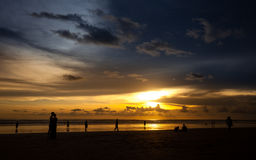 Silhouettez les personnes équipent une femme sur le coucher du soleil de fond photographie stock libre de droits