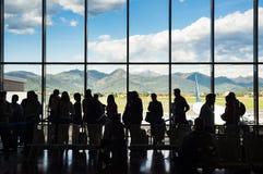 Silhouettez les personnes de file d'attente attendant sur le point d'avoir l'avion dans le terminal avec le fond de montagne Photo libre de droits