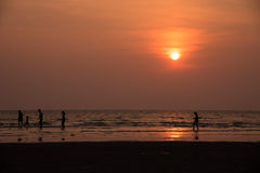 Silhouettez les personnes jouant sur la plage en mer Photo stock