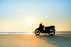 Silhouettez les supports d'une motocyclette sur la plage Image stock