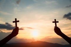 Silhouettez outre des mains tenant la croix en bois sur le fond de lever de soleil, le crucifix, symbole de la foi photo libre de droits