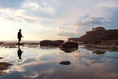 Silhouettez un homme marchant avec la réflexion sur l'eau sur l'île image stock
