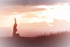 Silhouettieren Sie übendes Yoga der jungen Frau auf dem Berg bei Sonnenuntergang Stockfotos