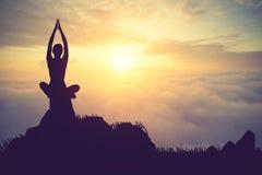 Silhouettieren Sie übendes Yoga der jungen Frau auf dem muontain bei Sonnenuntergang Lizenzfreies Stockfoto