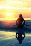 Silhouettieren Sie übendes Yoga der jungen gesunden Frau auf dem Strand stockfotografie