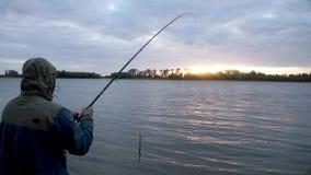 Silhouettieren Sie anziehende Fische des Fischers und spinnende Angelrolle während des Beißens