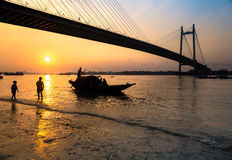 Silhouettieren Sie Boot bei Sonnenuntergang auf Fluss Hooghly mit Vidyasagar-setu Brücke am Hintergrund Stockfoto
