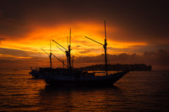 Silhouettieren Sie Boot und Sonnenuntergang Penisi in Sorong, West-Papua Stockbild