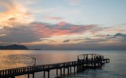 Silhouettieren Sie Brücke und pavillion auf dem Meer mit Leuten gehen auf t Stockfoto