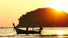 Silhouettieren Sie das Boot des langen Schwanzes, das in die Bootsexkursionen und -touristen schwimmen in das andaman Meer umgewa stock footage