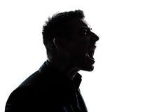 Silhouettieren Sie das Mannportrait-Profilschreien verärgert Stockfoto