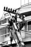 Schattenbildelektriker, der an Stromposten arbeitet Stockbild