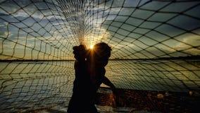 Silhouettieren Sie den Fischer, der das Netz am See im Moring, Thailand wirft Stockfotos