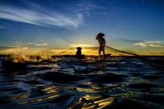 Silhouettieren Sie den Fischer, der das Netz am See im Sonnenuntergang trowing ist, Stockbilder
