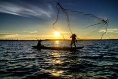 Silhouettieren Sie den Fischer, der das Netz am See vor Sonnenuntergang trowing ist Stockfotografie