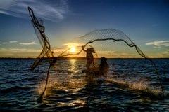 Silhouettieren Sie den Fischer, der das Netz am See vor Sonnenuntergang trowing ist, Stockbilder