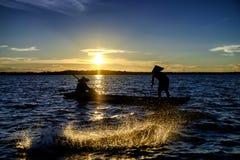 Silhouettieren Sie den Fischer, der das Netz am See vor Sonnenuntergang trowing ist, Stockbild