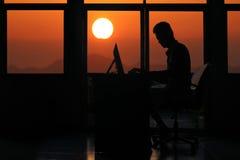 Silhouettieren Sie den Geschäftsmann, der an einem Computer mit Sonnenuntergang arbeitet Stockfoto