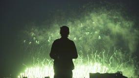 Silhouettieren Sie den jungen Fotografen, der auf Dach mit der Kamera steht, die Feuerwerke betrachtet stock footage