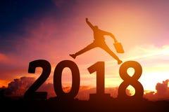 Silhouettieren Sie den jungen Geschäftsmann, der für 2018 neues Jahr glücklich ist Stockfotografie