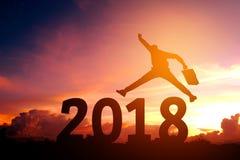 Silhouettieren Sie den jungen Geschäftsmann, der für 2018 neues Jahr glücklich ist Stockbild