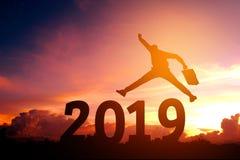 Silhouettieren Sie den jungen Geschäftsmann, der für 2019 neues Jahr glücklich ist Stockbild