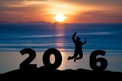 Silhouettieren Sie den jungen Mann, der auf das Meer und 2016 Jahre beim Feiern des neuen Jahres springt Lizenzfreie Stockfotografie