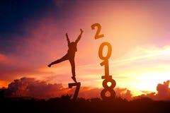 Silhouettieren Sie den jungen Mann, der für 2018 neues Jahr glücklich ist Stockfotografie