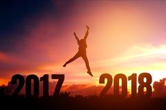 Silhouettieren Sie den jungen Mann, der für 2018 neues Jahr glücklich ist Stockfotos