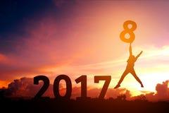 Silhouettieren Sie den jungen Mann, der zu 2018 neuem Jahr springt Stockfotografie