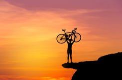 Silhouettieren Sie den Mann in anhebendem Fahrrad der Aktion über seinem Hauptstand auf den Berg mit Sonnenuntergang Stockfoto