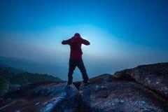 Silhouettieren Sie den Mann, der in Sonnenunterganghimmel steht Stockbilder
