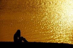 Silhouettieren Sie die alleinfrau, die auf der Rasenfläche nahe Wasser an sitzt Lizenzfreie Stockfotos
