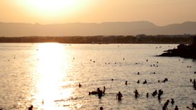 Silhouettieren Sie die Gruppe Reisendfreude entspannend und auf Strandküste zur Sonnenuntergangzeit springend, der im Freien Erfo stock video