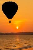 Silhouettieren Sie die Heißluftballone, die über tropischen Strand auf Sonnenuntergang schwimmen Stockfotos